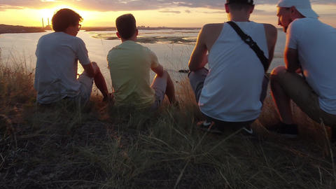4 friends sit on the edge of a cliff and watch the sunset. The guy shoots a GIF
