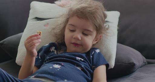 Portrait of a cute, funny little toddler girl at home eating a snack Acción en vivo