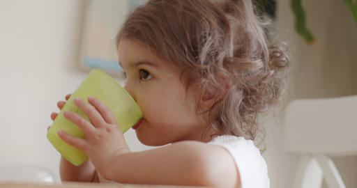 Portrait of a cute, funny little toddler girl at home drinking milk GIF