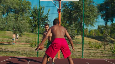 Sportsman dribbling ball at outdoor urban court Acción en vivo