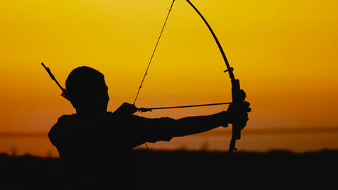 Archery silhouette, sun sets behind the archer Live Action