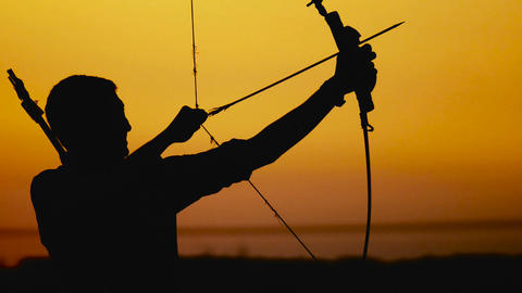 Archery silhouette, sun sets behind the archer. Young hunter Footage