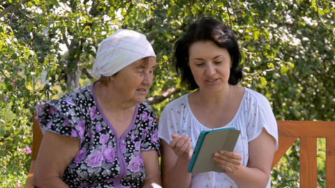 Young woman shows her elderly mother how to use the tablet Footage