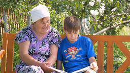Grandson reading a book to his grandmother Live Action