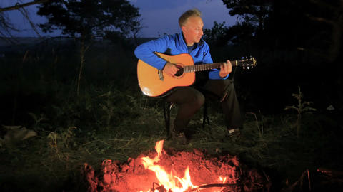 Man playing an acoustic guitar in the woods Footage