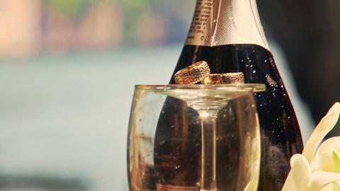 Champagne Bottle Tall Wine Glasses Wedding Rings on Top Footage