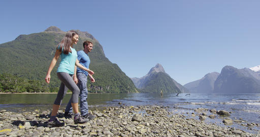Tourists hiking in New Zealand in Milford Sound by Mitre Peak in Fiordland Acción en vivo