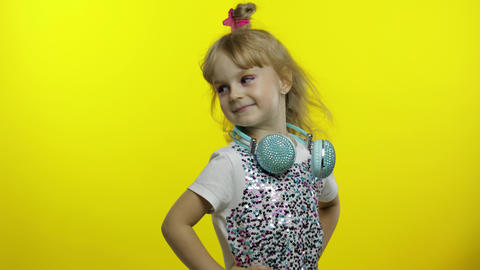 Child with headphones, showing thumb up. Relaxing, enjoying, having hun on Live Action