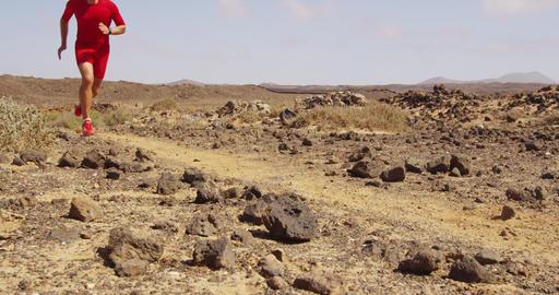 Running man trail running in desert - male runner running fast Acción en vivo