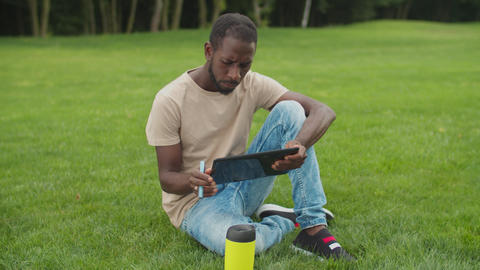 African man networking on tablet pc outdoors Acción en vivo