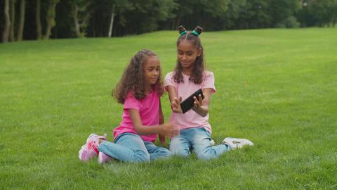 Cute girls making video call on cellphone in park Acción en vivo