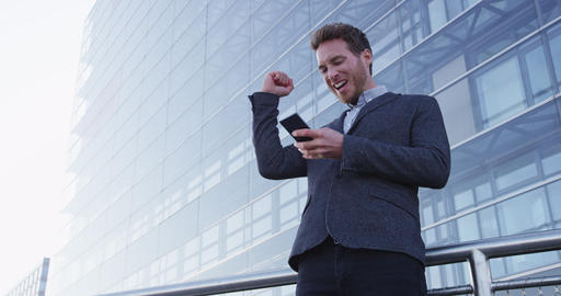 Business success and achievement - happy businessman cheering with cell phone Acción en vivo
