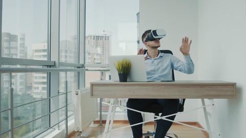 A young man sitting at a desk in the office uses augmented reality glasses to Live Action