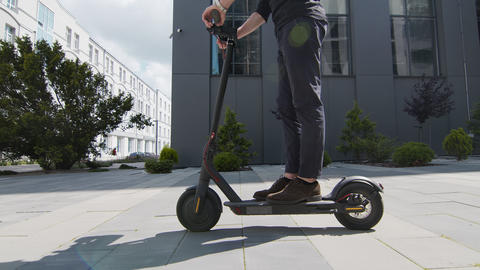 legs of a man riding an electric ecological scooter. A man stands on the Live Action