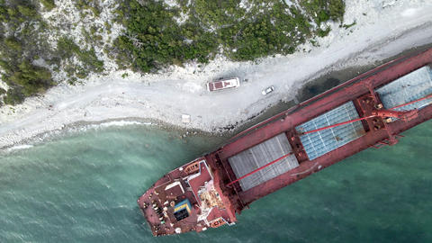 Cargo ship standing at shoal of sand beach after run aground Live Action