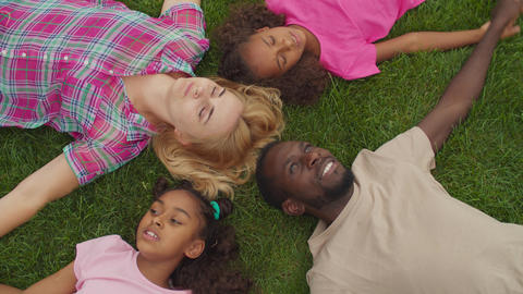 Diverse family lying head to head in circle on grass Live Action