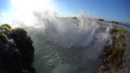 Near view, splashes between the rocks at the coast, slow motion Footage