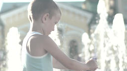 Child near the fountain during the day. Slow motion Footage