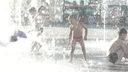 Children play with the fountain water in the summer . Slow motion Footage