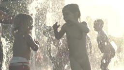 Childhood. Children play with water jets in the fountain Footage