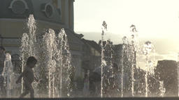 Children near the fountain in the evening, in the summer at sunset . Slow motion Footage