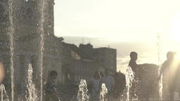 Silhouettes of people near the fountain in the evening, in the summer at sunset Footage