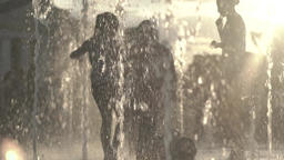 Kids having fun in the fountain in the summer at sunset . Slow motion Footage