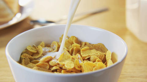 Pouring Milk into a Bowl with Corn Flakes Footage