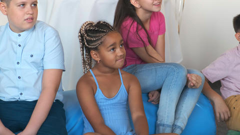 African-American girl with friends watches show at birthday Live Action
