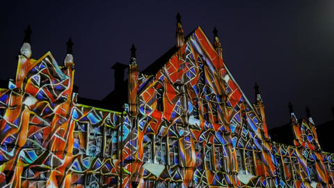 Colorful video mapping show projected on wall of historical building on street Live Action