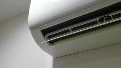 Air Conditioner on the wall is working which wind blade moving and swinging to provide cool wind to Live Action