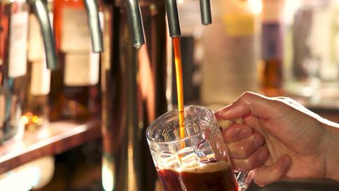 Dark beer filling and overflowing bartender pouring dark craft beer Live Action