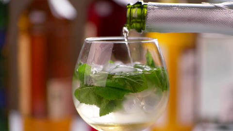 Bottle pours drink into wineglass mint leaves in bubbly drink Live Action