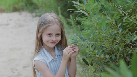 A beautiful girl stands by the green bushes. Portrait of a little girl Live Action