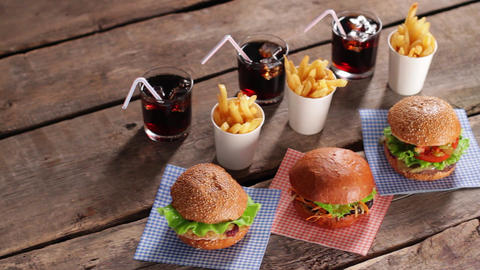Junk food with cold drinks burgers and cola on table Live Action
