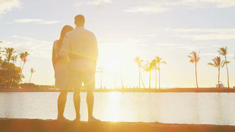 Romantic sunset happy couple in love enjoying summer vacation sunlight at beach Live Action