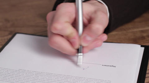 Male hand signing a document hand with pen signs paper Live Action