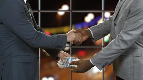 Men in suits shake hands businessmen passing dollar bundles financial deal Live Action