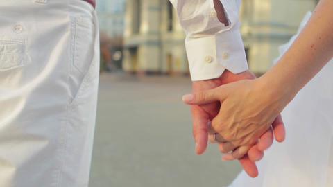 Bride and groom hold each others hands the newlyweds tenderly holding hands Live Action