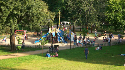 Outdoor playground in the park kids and their parents in the summer park Live Action