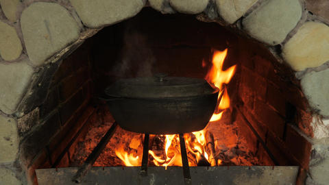 Cooking food in the oven on an open fire. Cast-iron cauldrons with food Live Action