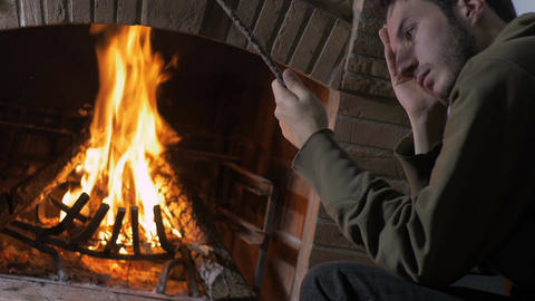 young man sat at home near a fire place, plays pensively with a stick Footage