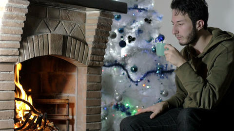 young man in pensive attitude sips a cup of tea, fireplace Footage