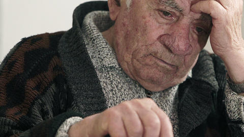 worried pensioner takes his head with hand and keeps other hand on his stick Live Action