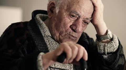 thoughtful pensioner takes his head with hand and keeps other hand on his stick Live Action