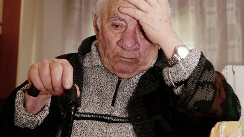 Elderly man sit on his armchair thinking sadly Live Action