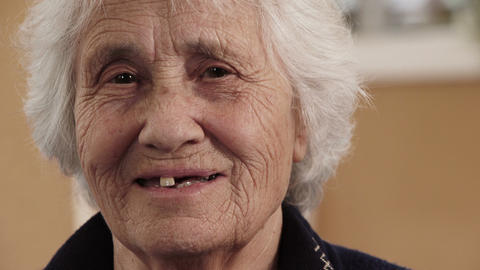 Tender old woman laughs looking at the camera Footage
