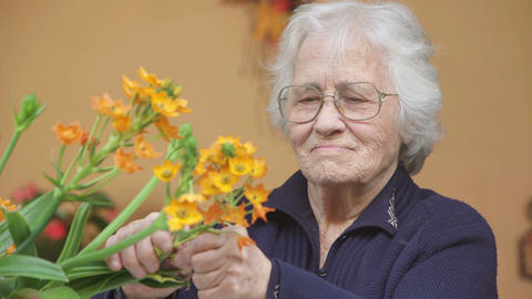 Old woman takes care of her flowers Footage