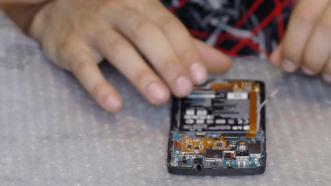 Focus on Technician hands while disassembling a component of a smartph Live Action