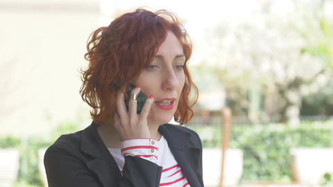redhead woman talking at her mobile phone, smiling and cheerful Footage